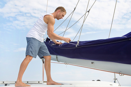 Attractive man standing on a sailing boat. photo