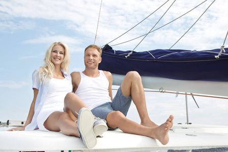 Handsome couple sitting on sailing boat - love. photo