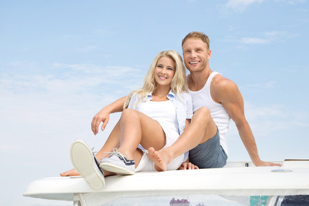Handsome couple sitting on sailing boat. photo