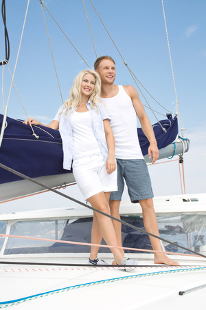 Handsome couple standing on sailing boat - sailing trip. photo