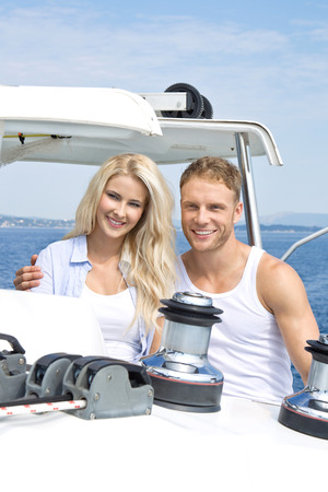 Couple standing on sailing boat - sailing trip. photo