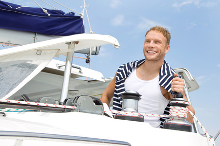skipper: Attractive young man on sailing boat. Stock Photo