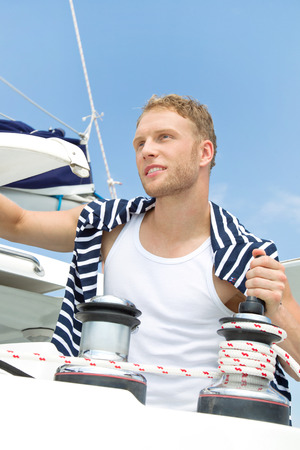 Attractive young man on sailing boat. photo