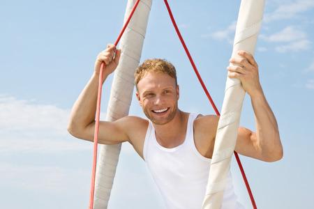 Blonde knappe jonge man op zeilboot.