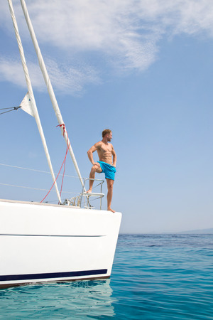 Blond attractive young man posing on sailing boat. photo