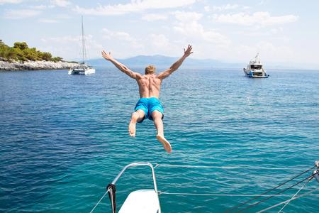 Man jumping from a sailing boat.