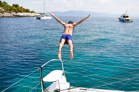 persona saltando: El hombre que salta de un barco de vela.