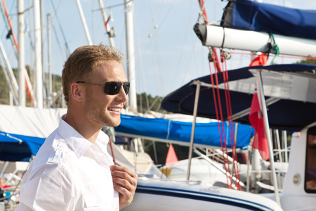 skipper: Handsome young man at seaport in front of sailing boat - harbor