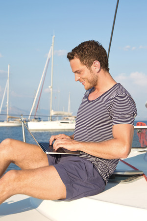 Manager is working with laptop during vacation on a sailboat   photo