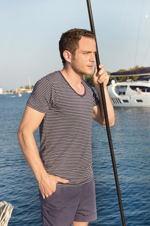 Attractive man standing on a sailing boat  photo