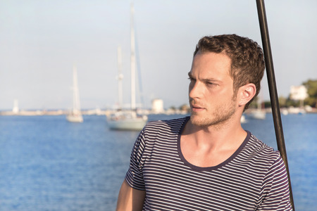Handsome man standing on a sailing boat  photo