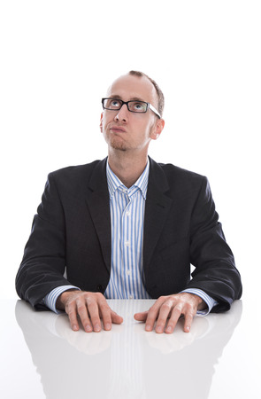 Isolated business man with glasses at desk is thinking about something   Stock Photo