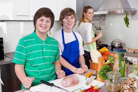 Mother is teaching her sons how to cook.  Stock Photo