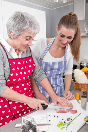 golden ager: Daughter cooking with her mother at kitchen.  Stock Photo