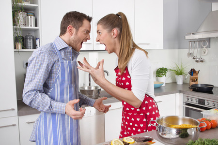 Man and woman shouting at each other at kitchen.  photo