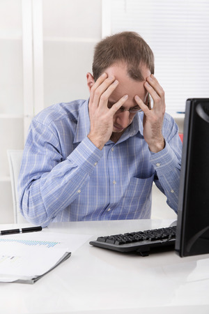 Overworked manager frustrated and stressed in his office with computer.  Stock Photo