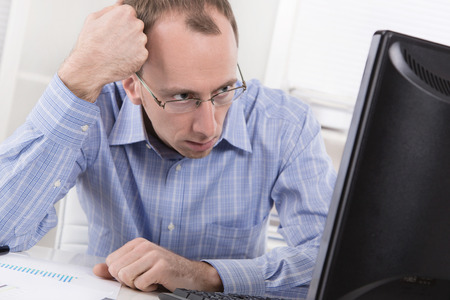 demotivated: Overworked manager frustrated and stressed in his office with computer.  Stock Photo