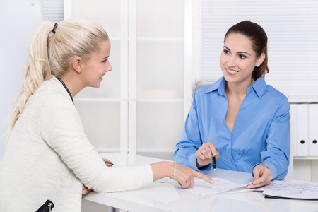 interviewing: Two colleagues talking together at desk at office - application or interview.