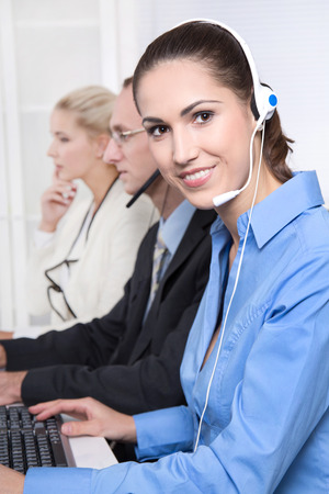 customer facing: Call Center: telesales or helpdesk team - helpful woman with headset smiling at camera.  Stock Photo