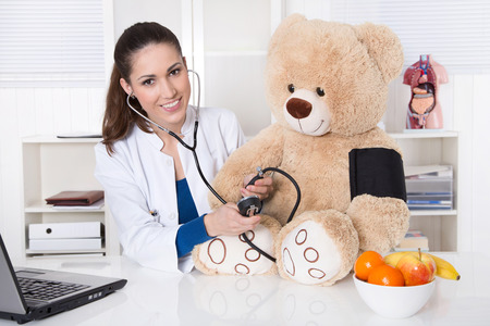 Young doctor for children is measure blood pressure on a teddy bear   photo