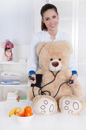 Occupation  young female doctor for children with a teddy bear  photo