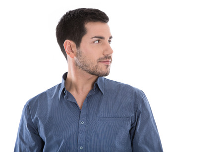 Isolated portrait of attractive young man looking sideways in blue shirt  Stock Photo