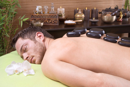 tenseness: Man at spa getting a hot stone massage Stock Photo