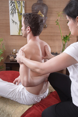 tenseness: Pressure point massage - man with female masseur at traditional thai massage