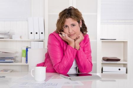 demotivated: Frustrated businesswoman sitting at desk at office. Stock Photo