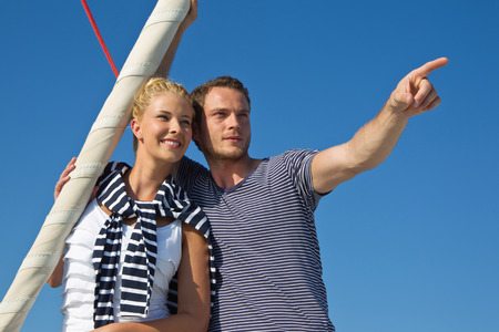 Handsome male pointing with forefinger at something - couple on sailing boat. photo