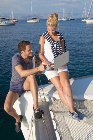 Working couple with laptop on sailing boat. photo