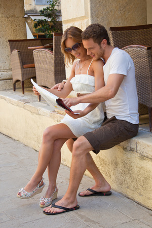 Sitting attractive couple looking at road map. photo