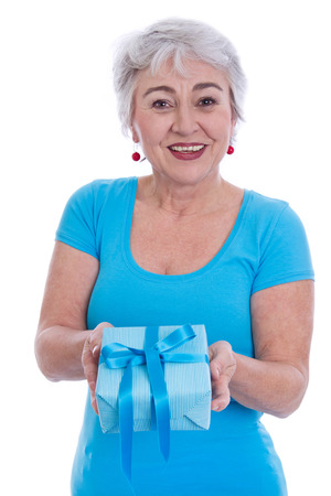 Older woman isolated in white with a turquoise shirt holding a gift box. photo