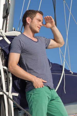 Handsome male on sailing boat looking for something in the distance. photo