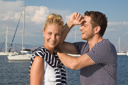 Happy handsome couple posing on sailing boat. photo