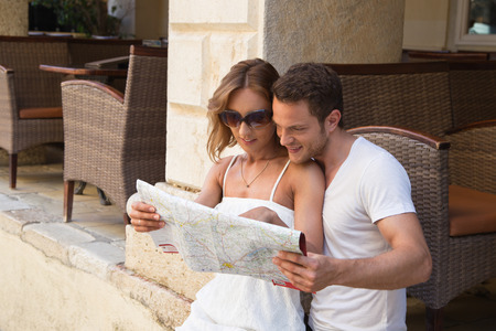 route map: Attractive couple looking at route map.