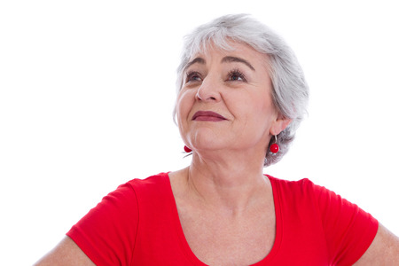 Face of a happy senior woman in red isolated on white .