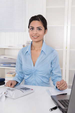 Young indian woman sitting at desk in her office with a blue blouse. photo