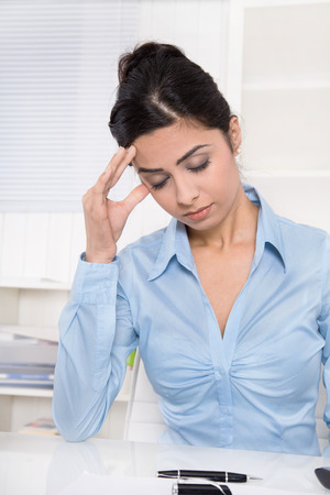 Pretty young asian secretary has migraine or headache at office.