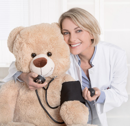 1 person: Portrait of mature blond medical doctor in uniform with a teddy bear.