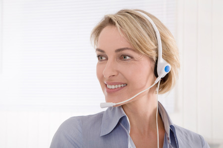 Mature businesswoman looking sideways with headphone. photo