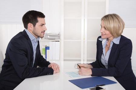 dos personas hablando: Entrevista en la oficina con la empresaria y el joven aprendiz guapo. Foto de archivo
