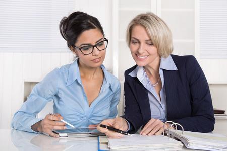 women talking: Successful teamwork under businesswoman at desk