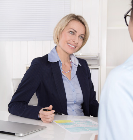 blazer: Interview with young female and mature manager at office  Stock Photo