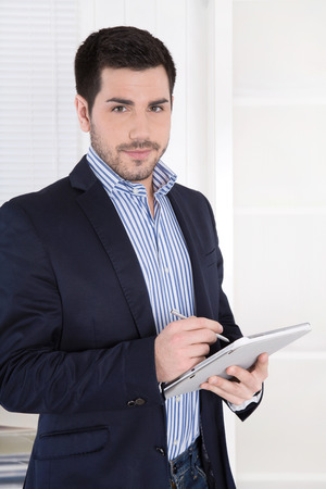 Portrait of a modern successful young businessman with tablet-pc in the office  Stock Photo