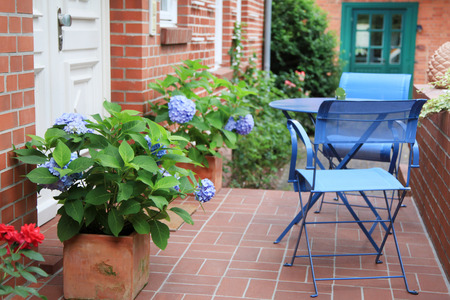 the flair: Close up from house facade with white front door, flowers and blue chairs with table.