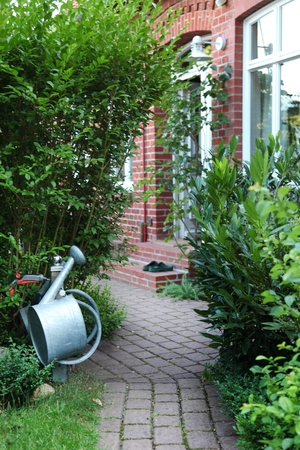 path cottage garden: Cottage garden: paved path with a old farmhouse . Stock Photo