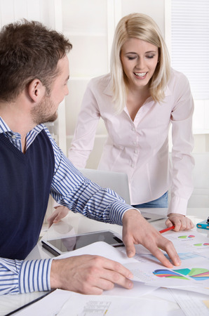 Entrepreneur shows his secretary his diagrams at office  photo