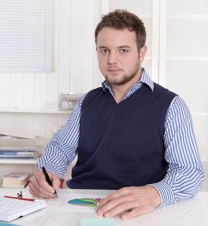 outgoings: Attractive academic working with diagrams at office. Stock Photo