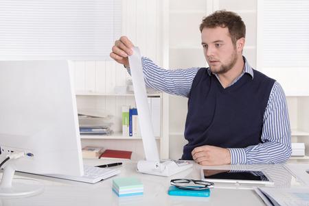 economist: Handsome economist with calculating machine at desk
